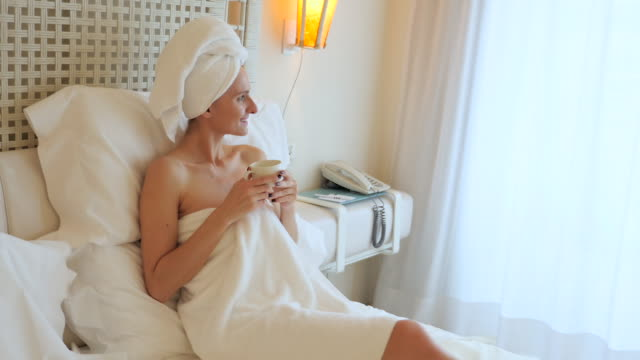 relaxing in bed after spa treatment - wearing a towel stock videos and b-roll footage
