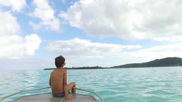 vídeos de stock e filmes b-roll de relaxing in boat on water - ilha huahine