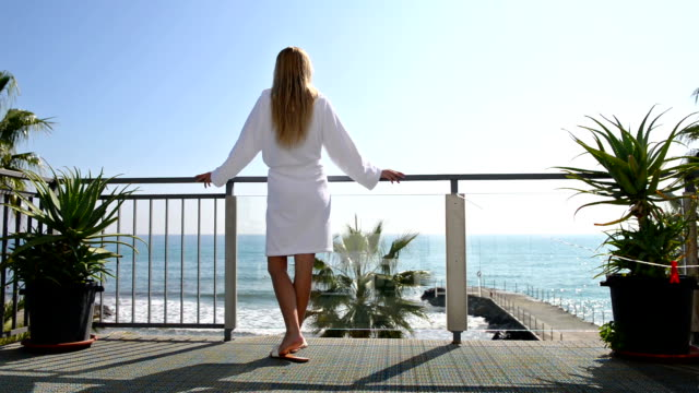 relaxing in hotel balcony with scenic sea view - bathrobe stock videos & royalty-free footage
