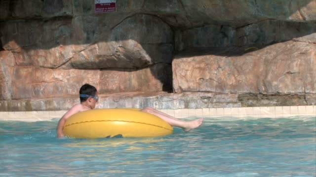 relaxing in the pool - water slide stock videos & royalty-free footage