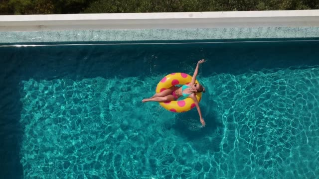 relaxing in the pool - galleggiare sull'acqua video stock e b–roll