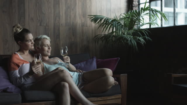 relaxing lesbian couple drink wine on couch, medium shot - camisole stock videos & royalty-free footage