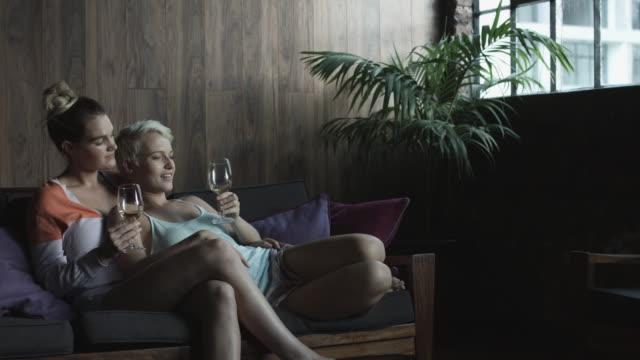 vídeos y material grabado en eventos de stock de relaxing lesbian couple drink wine on couch, medium shot - camisola