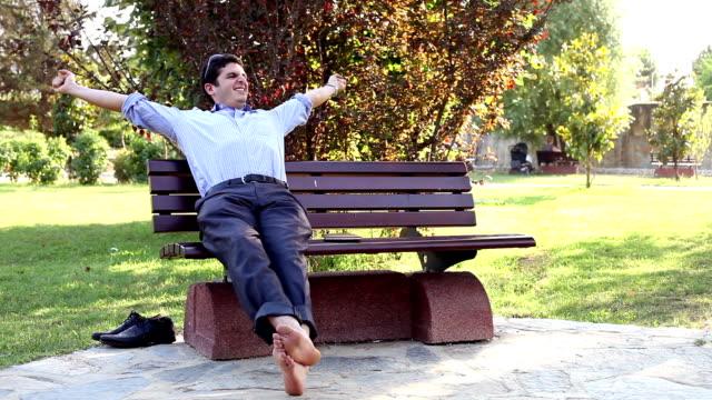 vídeos de stock e filmes b-roll de descontrair no banco de parque, depois de um árduo dia de trabalho - banco de parque