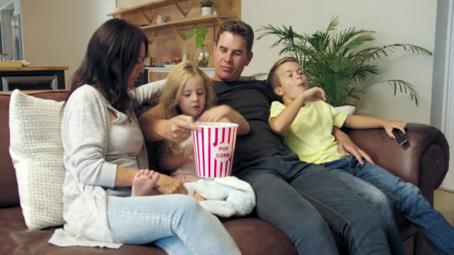 relaxing on sofa and eating popcorn - 45 49 anni video stock e b–roll