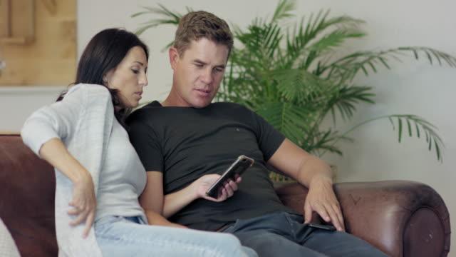 vídeos de stock, filmes e b-roll de relaxing on sofa - casal de meia idade
