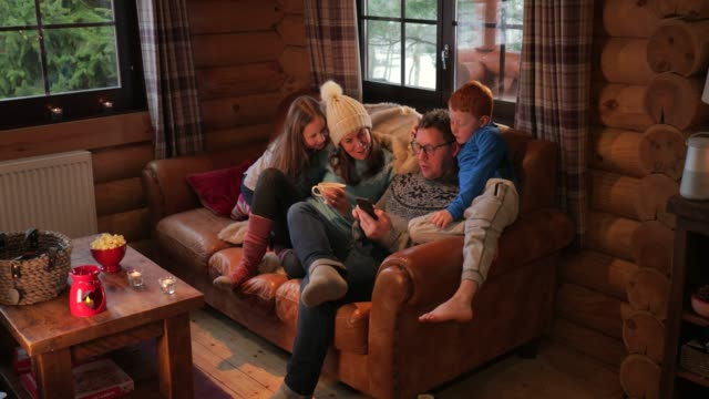 relaxing on the sofa with his family - ski holiday stock videos & royalty-free footage