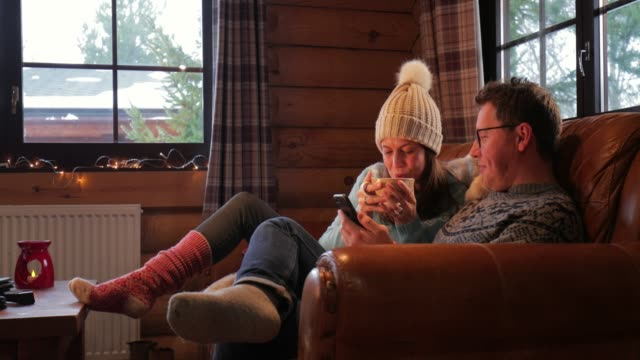 relaxing on the sofa with his wife - capanna di legno video stock e b–roll