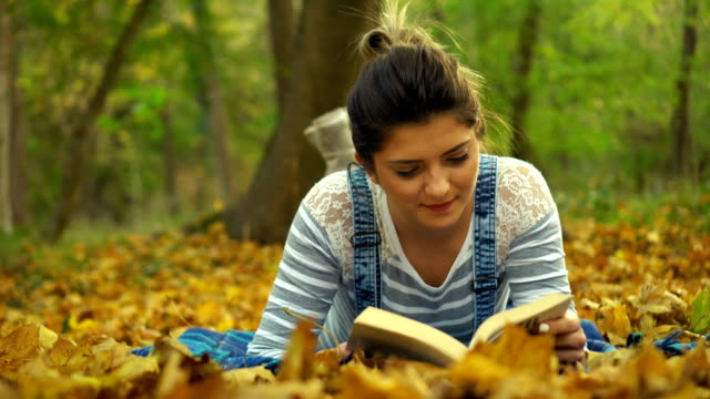relaxing with a good book in forest - bretella video stock e b–roll