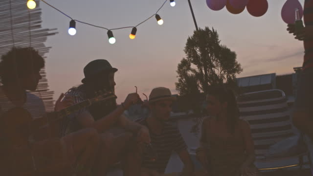 relaxing with friends at rooftop party - patio stock videos & royalty-free footage