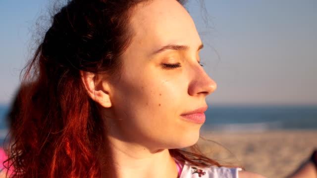 stockvideo's en b-roll-footage met ontspannen met yoga op het strand - strekken