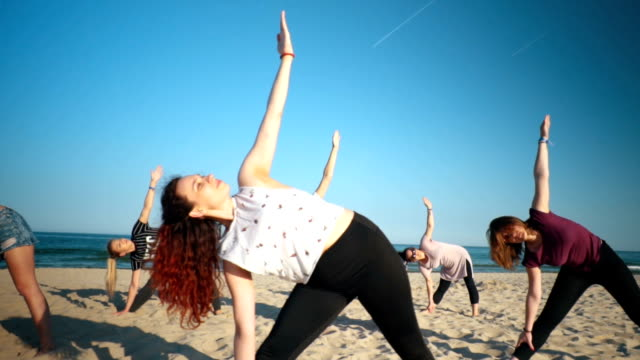 relaxing with yoga on the beach - serene people stock videos & royalty-free footage