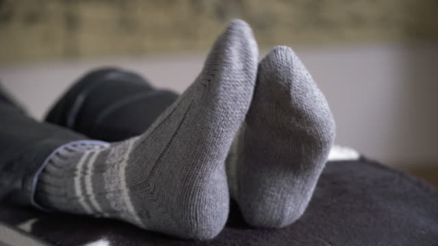 relaxing woman rubbing her feet together (4k/uhd) - sock stock videos & royalty-free footage
