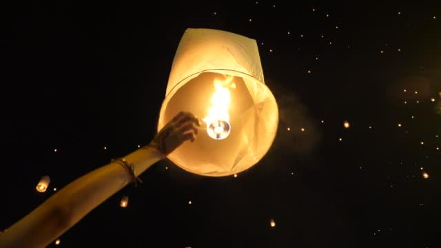 vídeos de stock e filmes b-roll de release flying lantern in yi peng festival, thailand - lanterna de papel