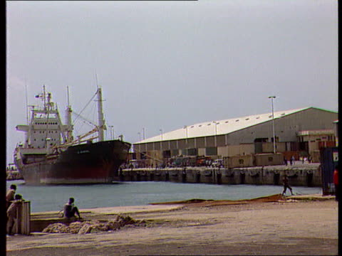 relief ship shelled; england gv boat in dock ) tx 24.8.92 tms people fighting in dock area and firing guns ) itn tx 24.11.92/nat - somalia stock videos & royalty-free footage