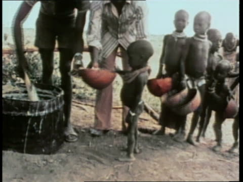 vídeos de stock e filmes b-roll de relief workers feed starving children in africa. - lagenaria