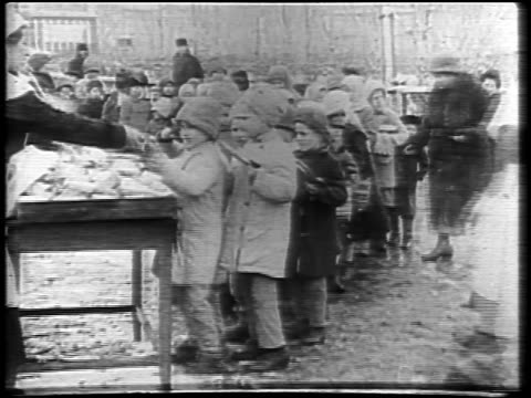 b/w 1921 relief workers giving food to line of children outdoors in winter / russia / newsreel - 1921 stock videos & royalty-free footage