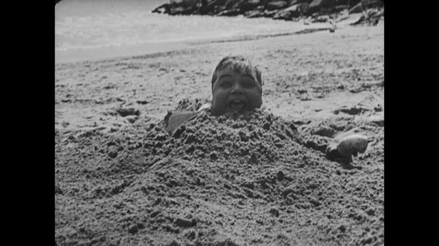 1917 Relieved and happy man (Fatty Arbuckle) hiding in sand, uses periscope to check that his wife has left before running away