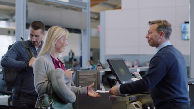 relieved family members scan boarding passes with smiling flight attendant at terminal gate. - gate stock videos & royalty-free footage