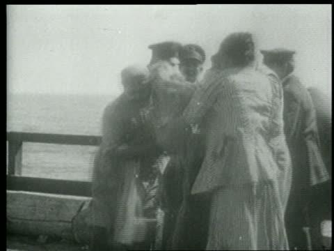 b/w 1915 relieved people + keystone kops on edge of pier comforting wet woman pulled from water - 1915年点の映像素材/bロール
