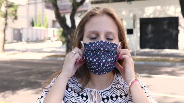 relieved woman removing her protective mask - removing stock videos & royalty-free footage