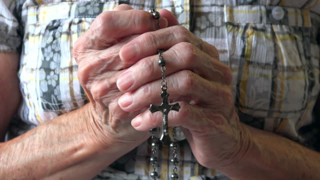 vídeos de stock, filmes e b-roll de religion: hands of a senior christian woman praying with a rosary - só uma mulher idosa