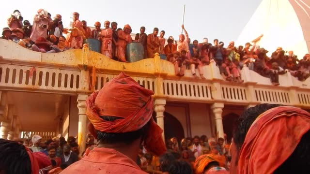religious festivities and celebrations a inside a temple complex in nandgaon, mathura, the village of lord krishna. holi or the festival of colours,... - 水鉄砲点の映像素材/bロール