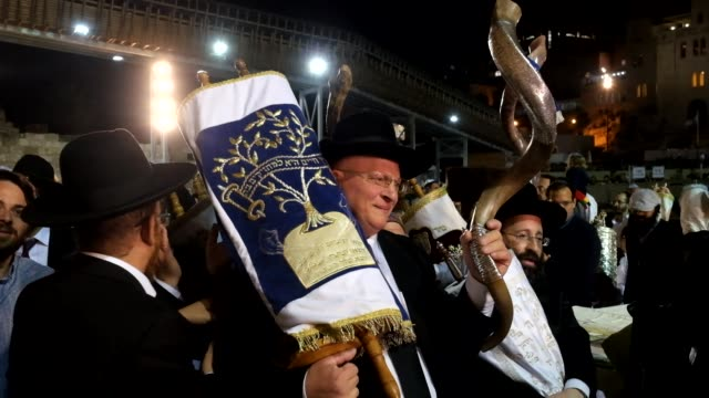 religious jews dancing with scrolls of torah as they celebrate the simchat torah a jewish holiday that celebrates and marks the conclusion of the... - torah stock videos and b-roll footage