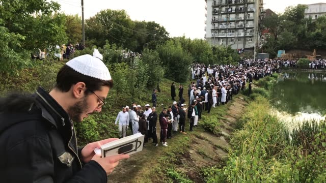 religious jews perform tashlikh, a jewish atonement ritual, at the bank of a lake formed by the umanka river on the first day of rosh hashanah on... - rosh hashanah stock videos & royalty-free footage