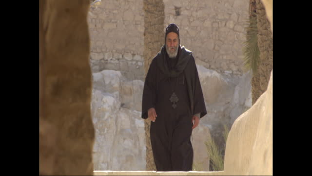 a religious man in black clothing walks down stone steps. - schwarzes hemd stock-videos und b-roll-filmmaterial