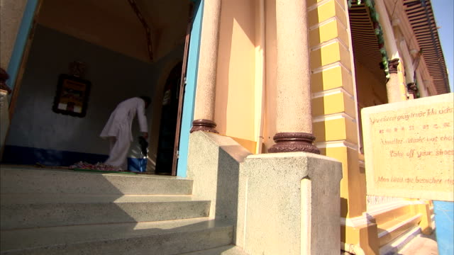 a religious man in white clothing drops a pair of men's shoes outside the entrance into cao dai temple. - tay ninh stock videos & royalty-free footage