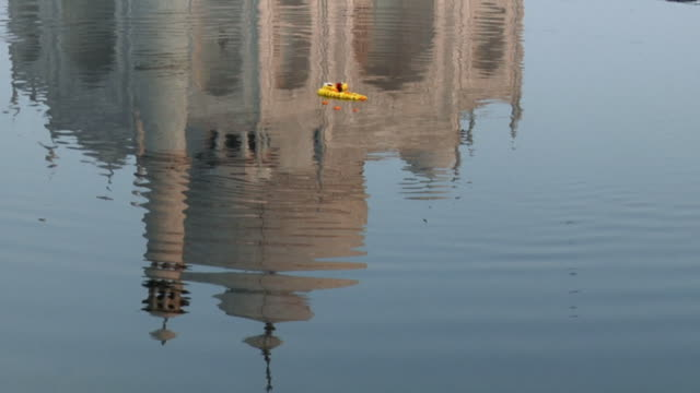 MS Religious offering of flowers floating above reflection of Taj Mahal in River Yamuna / Agra, Uttar Pradesh, India