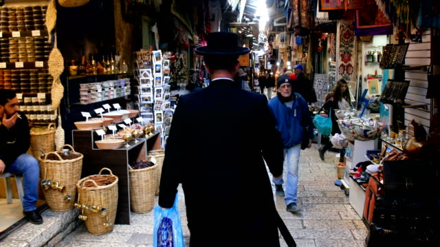 vídeos de stock e filmes b-roll de religious orthodax man walking in old city alleys, over the shoulder view, close-up/ jerusalem old city - sobre os ombros vista traseira