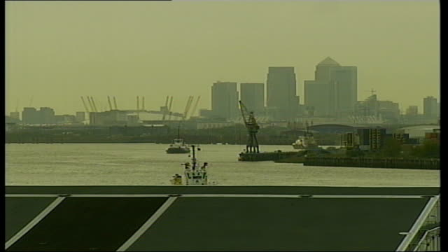 hms illustrious arrives in london river thames millennium dome and high rise city buildings seen through mist beyond flight deck of ship pull out to... - 船の一部点の映像素材/bロール