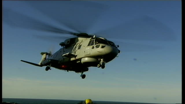 hms illustrious arrives in london england english channel illustrious 91106 merlin helicopter taking off from deck of ship tilt up air view of... - 船の一部点の映像素材/bロール