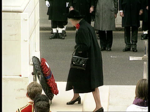 london whitehall queen carrying wreath rl pan rl as to cenotaph and lays wreath pull out as steps back as 'last post' heard sof 
