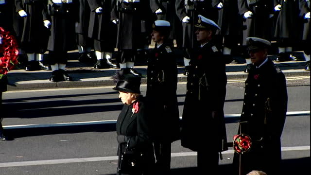 remembrance sunday service at cenotaph **music heard sot** gun fired to mark end of silence then last post playing / queen standing in front of... - remembrance sunday stock videos and b-roll footage