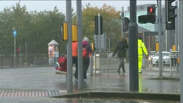 remnants of hurricane gonzalo hit uk; england: west yorkshire: leeds: day pedestrians hurrying along road in wind and rain gv workman cordoning off... - wet wet wet stock videos & royalty-free footage