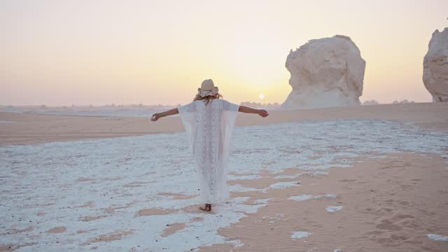 vidéos et rushes de remote adventure in the white desert of egypt - woman enjoys a walk through the sands while sunrise. - égypte