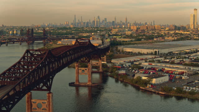 remote aerial view of manhattan, new york city, over general pulaski bridge - pulaski skyway, new jersey, at sunset. aerial drone video with the forward camera motion. - panning stock videos & royalty-free footage