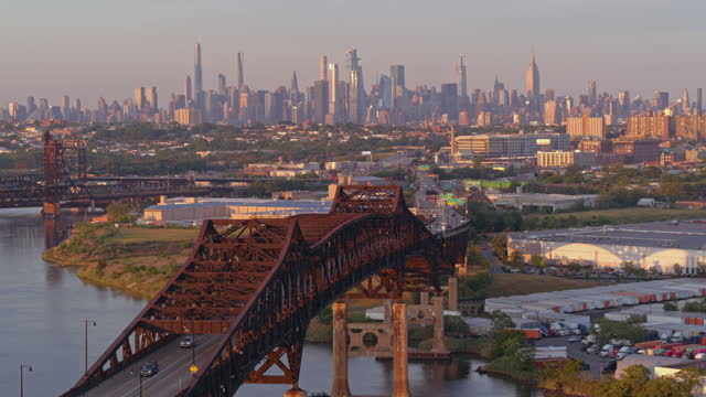 vídeos de stock e filmes b-roll de remote aerial view of manhattan, new york city, over general pulaski bridge - pulaski skyway, new jersey, at sunset. aerial drone video with the static camera - remote location