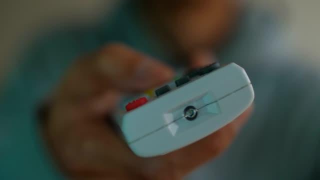telecomando nelle mani dell'uomo che punta alla tv - remote control video stock e b–roll