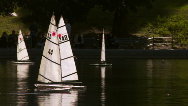 remote controlled boats in central park pond on a sunny day - floating on water stock videos & royalty-free footage