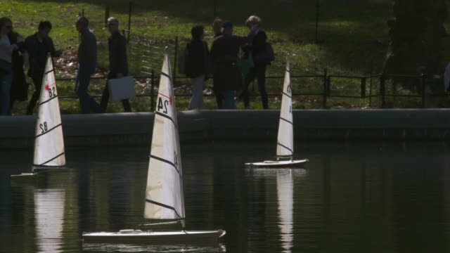 Remote controlled sail boats move past one another in slow motion in Central Park pond.