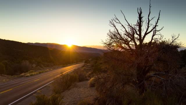 stockvideo's en b-roll-footage met afgelegen weg van de woestijn bij zonsondergang - time lapse - nevada