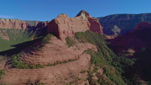vídeos de stock e filmes b-roll de remote scenic aerial view on the mountains in slide rock state park in sedona, arizona, from the scenic route 89a. drone video with the panoramic-orbit camera motion. - sedona