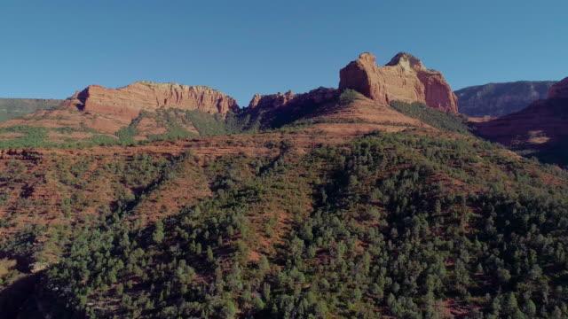 vidéos et rushes de vue aérienne panoramique à distance sur les montagnes dans slide rock state park à sedona, arizona, de la route panoramique 89a. drone vidéo avec le mouvement de la caméra descendante. - sedona