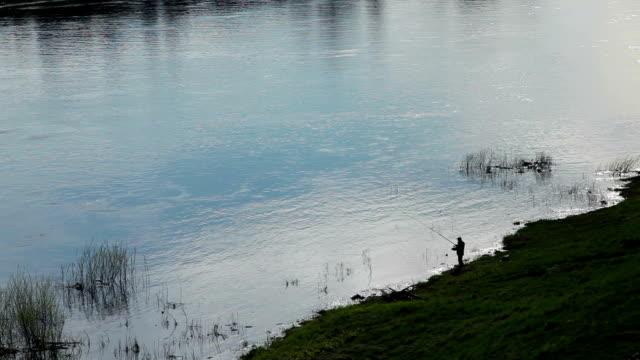 Remote-Ansicht einer Silhouette des Fischers Angeln im Fluss