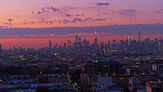 remote view of the manhattan skyline illuminated in the night over the residential district of bushwick, brooklyn, in the sunset. drone video with the panning-orbiting camera motion. - new york city stock videos & royalty-free footage