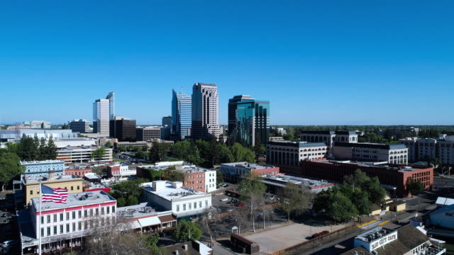 remote view to sacramento downtown over old sacramento waterfront district. aerial drone video with the forward camera motion. - sacramento stock videos & royalty-free footage
